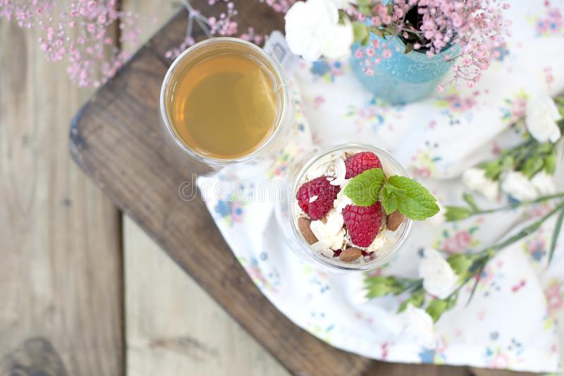 Useful breakfast of muesli and yogurt with berries in a glass. Tea in a glass. Wooden background and pink flowers. view from above stock image