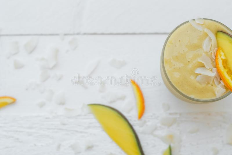 Useful breakfast: smoothies of mango, banana and orange on a white table. Top view, copy space stock photos