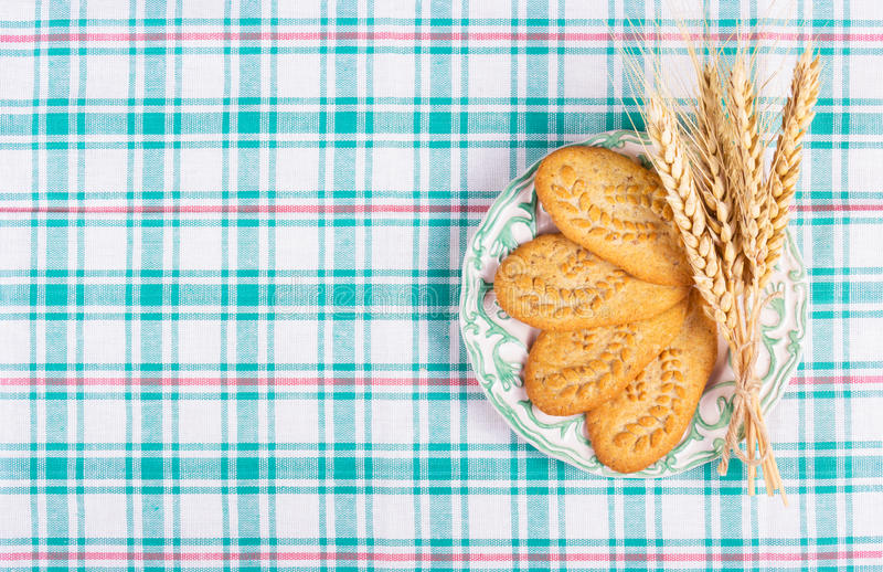 Useful cereal biscuits and wheat ears on a checkered tablecloth. Home breakfast. stock photos
