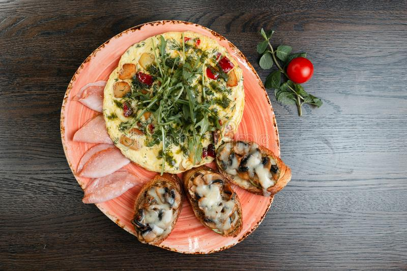 Useful frittata, delicious bruschetta with zucchini and fried mushrooms, ham fried on a wooden table in a restaurant. stock photography