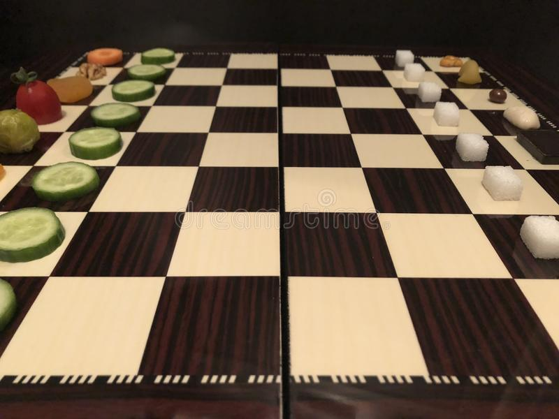 Useful and harmful foods play chess. Junk foods vs Vegetables. Useful and harmful foods play chess. Junk foods vs. Vegetables on the chessboard. It can use food stock images