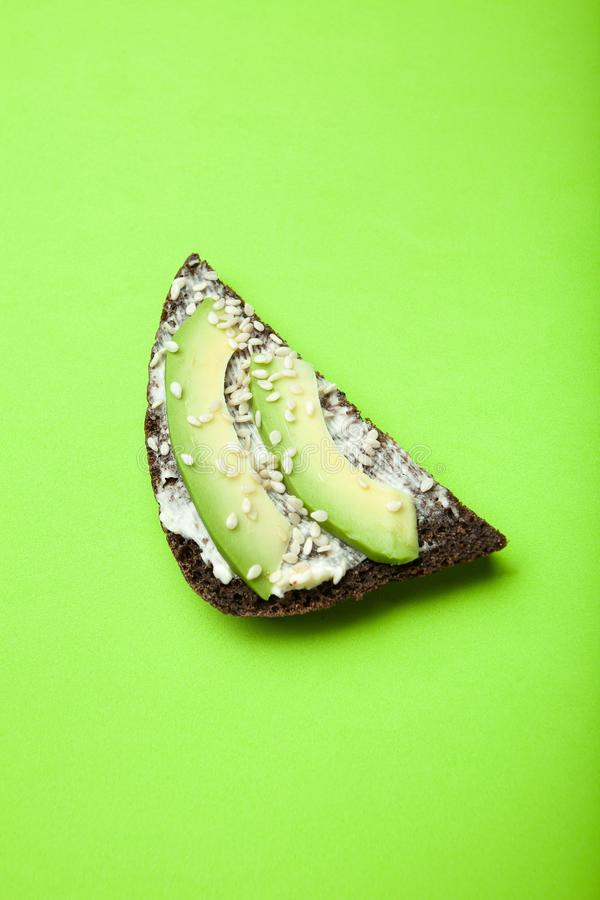 Useful sandwiches with avocado, cheese, sesame and black bread on a bright green background, vertically stock photos