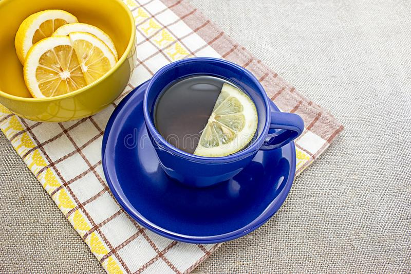 A useful therapeutic drink for colds. Fragrant lemon tea in a blue cup. A useful therapeutic drink for colds royalty free stock images
