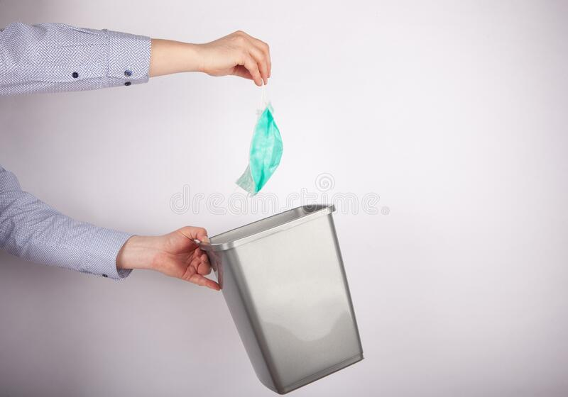 Useless coronavirus face mask - Man hands holding plastic trash can and putting a face mask in royalty free stock photo