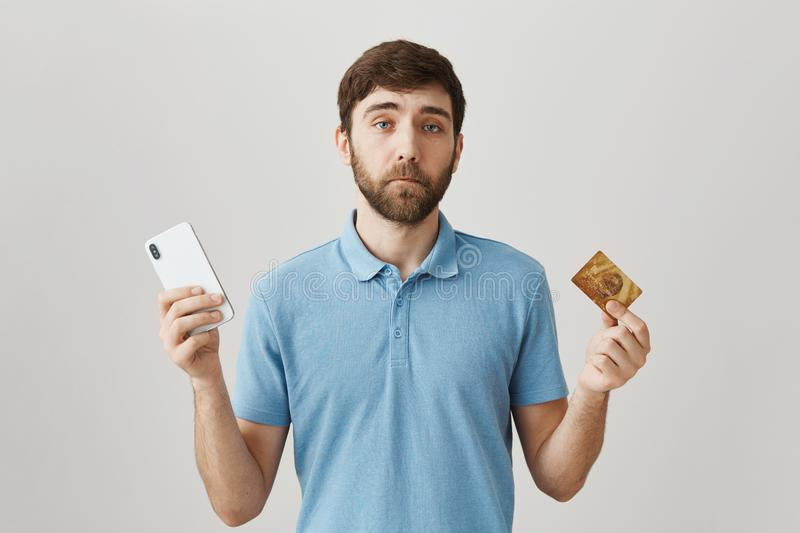 Useless credit card with low balance. Portrait of gloomy displeased young bearded guy holding smartphone and bank card. Having problems with payment online royalty free stock photo