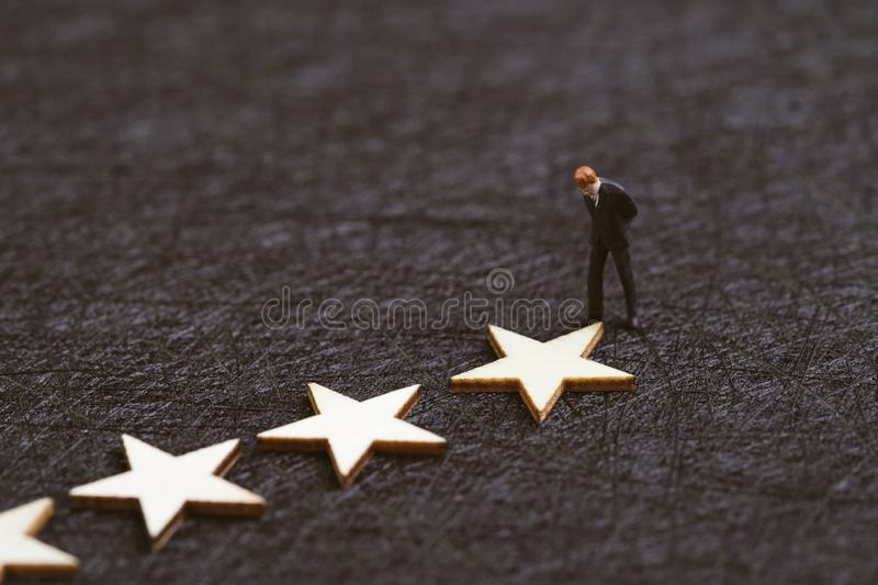 User experience, customer review or rating concept, miniature figure confidence businessman standing with stars on dark black. Background with copy space stock images