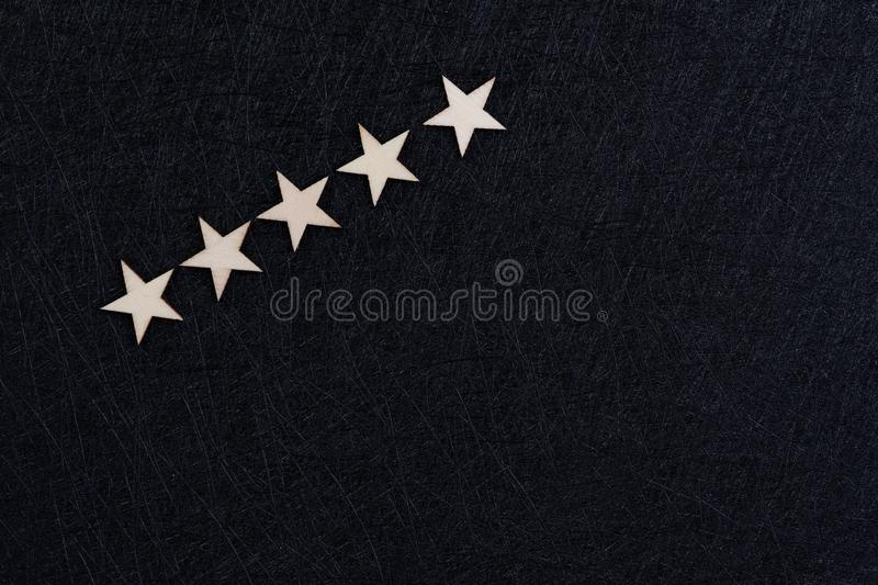 User experience, customer review or rating concept, 5 wooden stars on dark black background with copy space.  royalty free stock photo