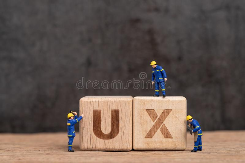 User Experience design in product and service concept, miniature people workers with blue team uniform building cube wooden block. With acronym UX on table with stock photos