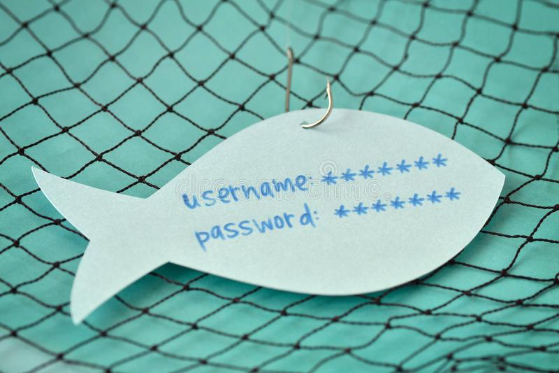 Username and password written on a paper note in the shape of a. Fish attached to a hook - Phishing and internet security concept stock photography