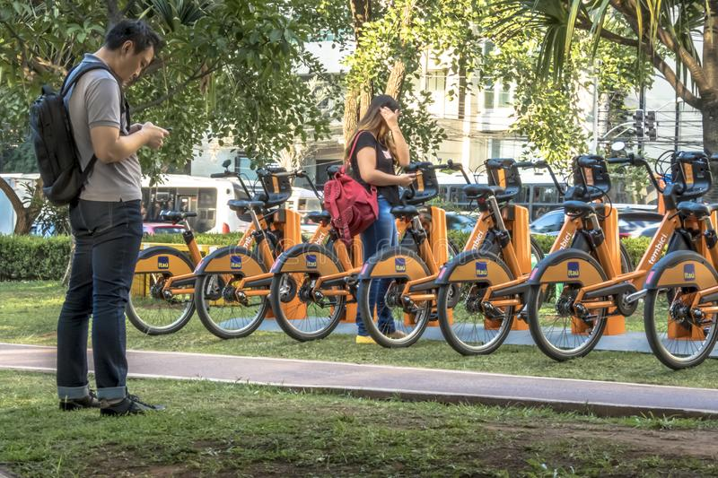 Users access the APP for Urban bikes for hire in Tembici Station of Bike in Faria Lima Avenue. Sao Paulo, Brazil, December 14, 2018. users access the APP for stock images