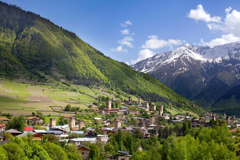 Ushguli village in Georgia, Svaneti region, ancient towers on a green hill high Caucasian mountains, mountain peaks in the snow royalty free stock image