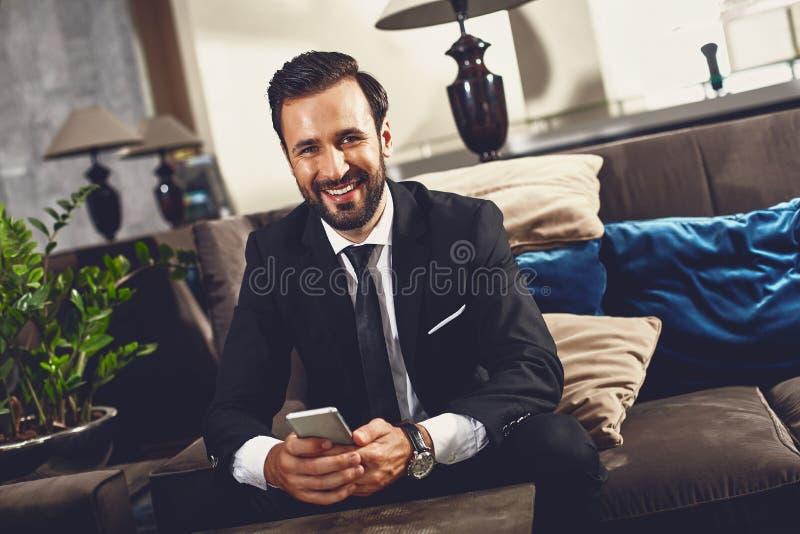 Usiądź na kanapie z smartfonem. obrazy royalty free