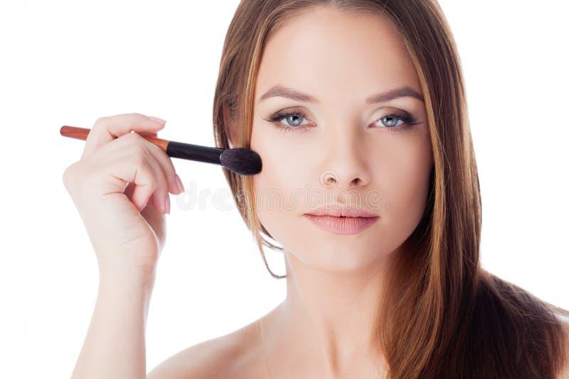 Usi la polvere Ragazza attraente che fa trucco Ritratto di bella giovane donna che usando una spazzola per il fondamento fotografie stock