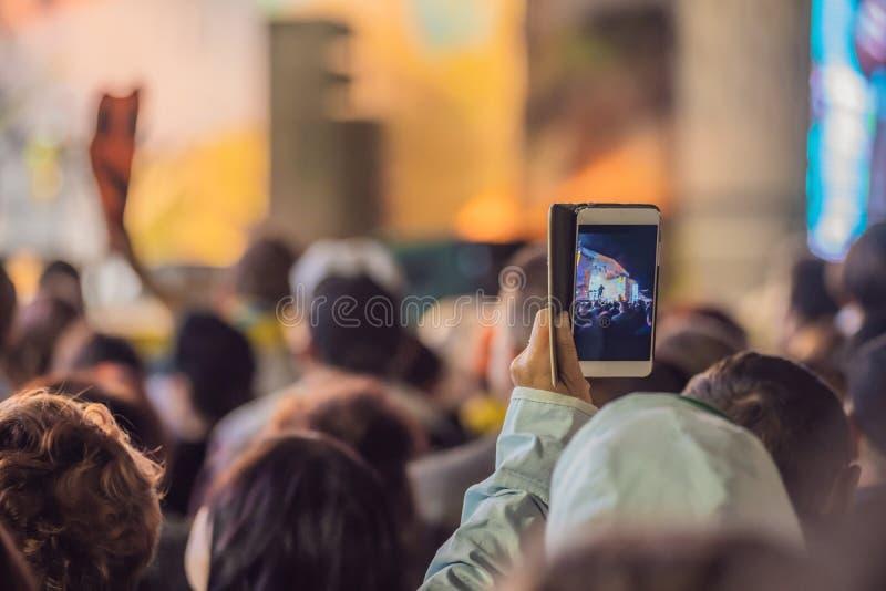 Usi la registrazione mobile avanzata, concerti di divertimento e la bella illuminazione, immagine schietta della folla al concert fotografie stock libere da diritti