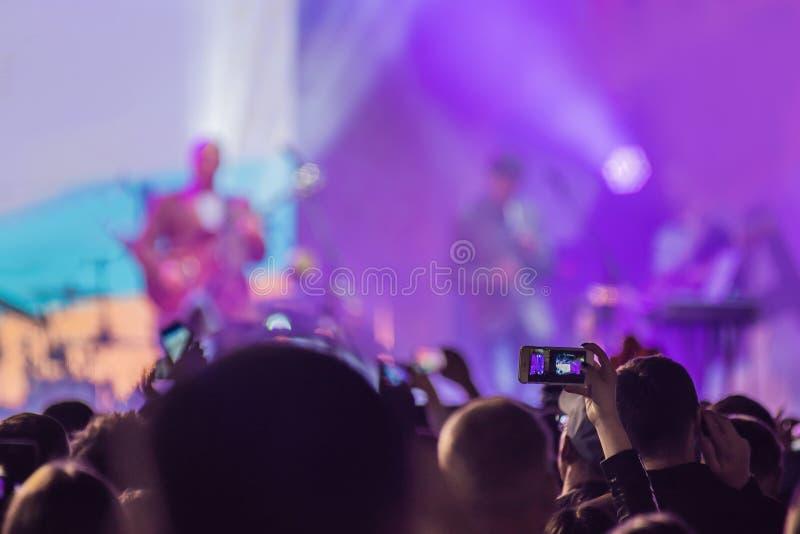 Usi la registrazione mobile avanzata, concerti di divertimento e la bella illuminazione, immagine schietta della folla al concert immagini stock