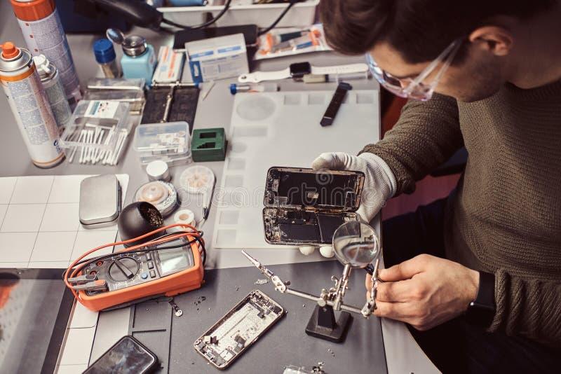 Usi lente e pinzette del meccanico riparare smartphone nocivo nell'officina fotografia stock libera da diritti
