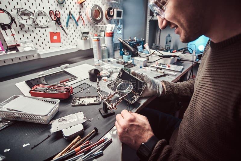Usi lente e pinzette del meccanico riparare smartphone nocivo nell'officina immagine stock libera da diritti