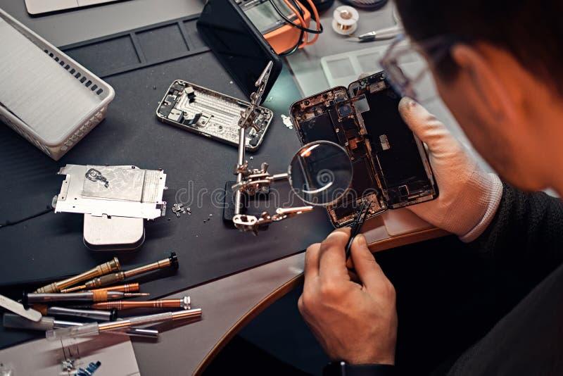 Usi lente e pinzette del riparatore riparare smartphone nocivo fotografia stock