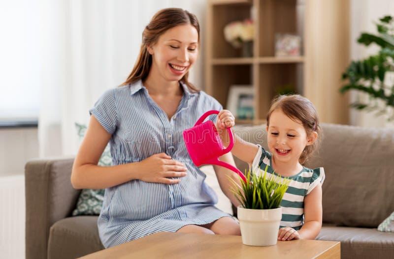 Usine à la maison de arrosage enceinte de mère et de fille photo stock