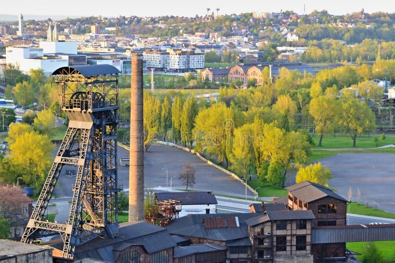 Usine abandonnée de ferronneries avec une tour et des arbres d'exploitation et ville à l'arrière-plan photo stock