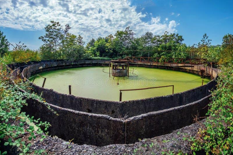 Usine abandonnée de traitement des eaux résiduaires Réservoir envahi de purification d'eaux d'égout avec de l'eau vert photos libres de droits