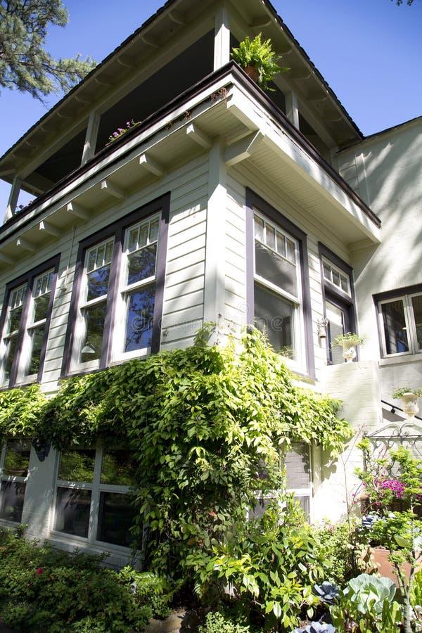 Usine autour d'une maison en bois de trois planchers photo libre de droits