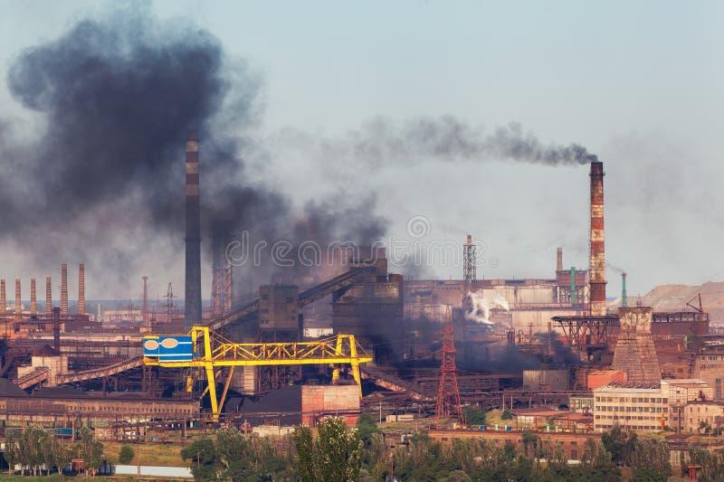 Usine en acier avec le brouillard enfumé au coucher du soleil Tuyaux avec de la fumée noire image stock