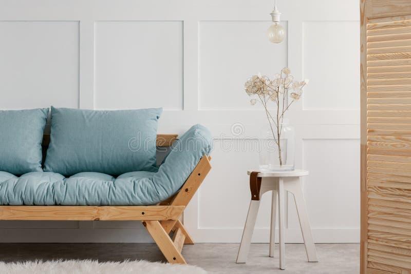 Usine et lampe sur le tabouret blanc à côté du sofa en bois bleu dans l'intérieur minimal de salon photos libres de droits