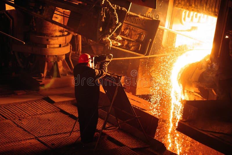 Usine pour la production de l'acier Un four de fonte électrique L'ouvrier pr?l?ve un ?chantillon pour le m?tal image libre de droits
