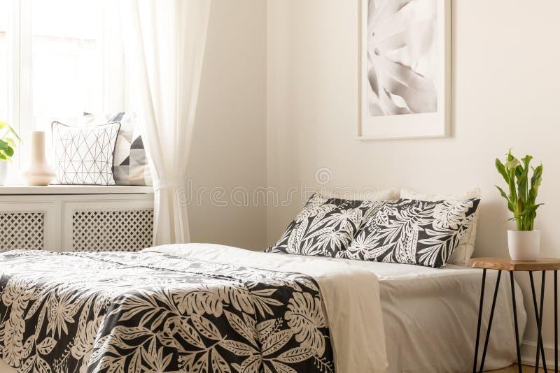 Usine sur la table à côté du lit avec les feuilles modelées dans le bedro lumineux photo stock