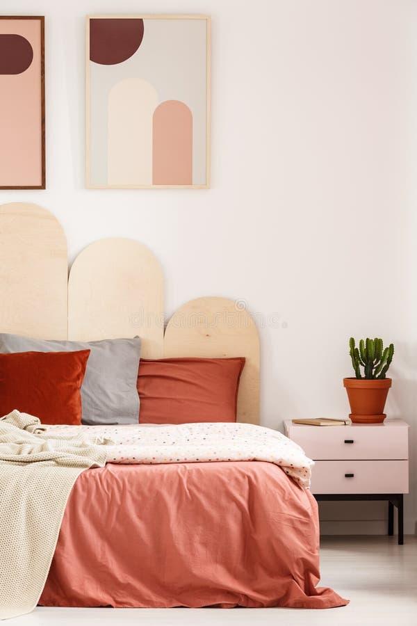 Usine sur le coffret à côté du lit avec des oreillers dans les WI intérieurs de chambre à coucher photographie stock libre de droits