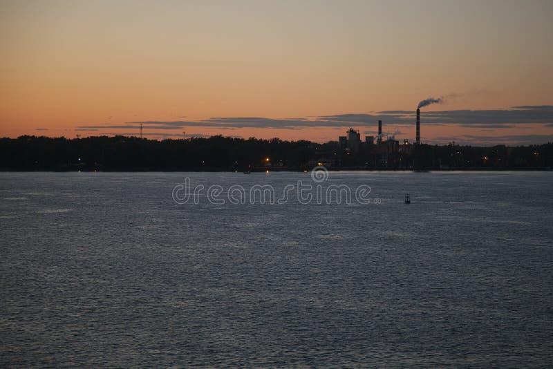 Usines avec des cheminées de smokey par la rivière au coucher du soleil photos libres de droits