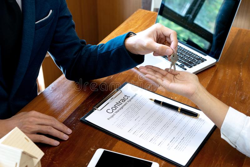 Usiness man agreement to sign for contract. Businessman Sale man for house broker show and give home key to the customer ,buy from agent, residential, hand royalty free stock image