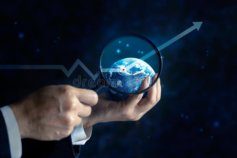 Usiness man looking a business graph upwards on globe and stars by use magnifying glass in hands, business concept, soft focus and stock photo
