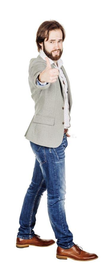Usinessman смотря камеру и показывая его большой палец руки вверх пока stan стоковое изображение