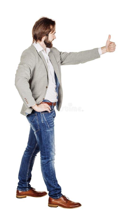 Usinessman смотря камеру и показывая его большой палец руки вверх пока stan стоковое фото