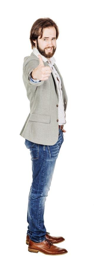 Usinessman смотря камеру и показывая его большой палец руки вверх пока stan стоковая фотография