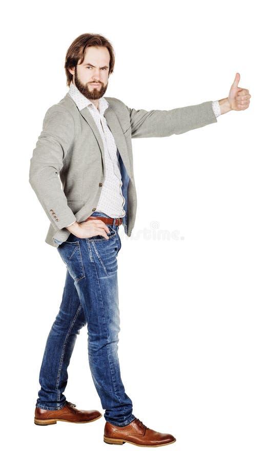 Usinessman смотря камеру и показывая его большой палец руки вверх пока stan стоковые изображения