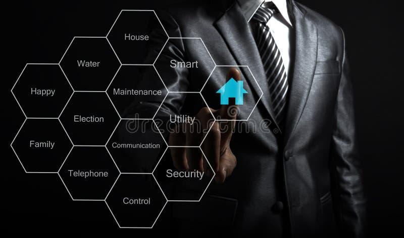 Usinessman wat betreft het slimme concept van de huisautomatisering royalty-vrije stock afbeelding