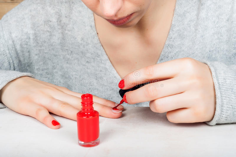 Using applicator brush to apply red polish to fingernail, self m. Ade manicure at home stock images