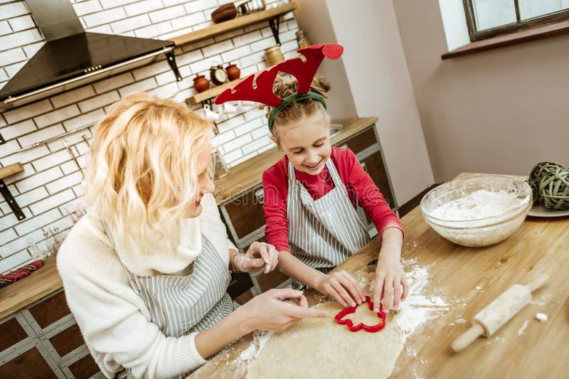 Smiling positive little child in striped apron learning cooking aspects royalty free stock photography