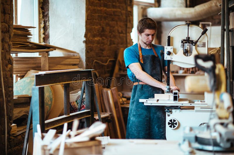 Using band-saw. Cabinetmaker processing workpiece with band-saw royalty free stock photography