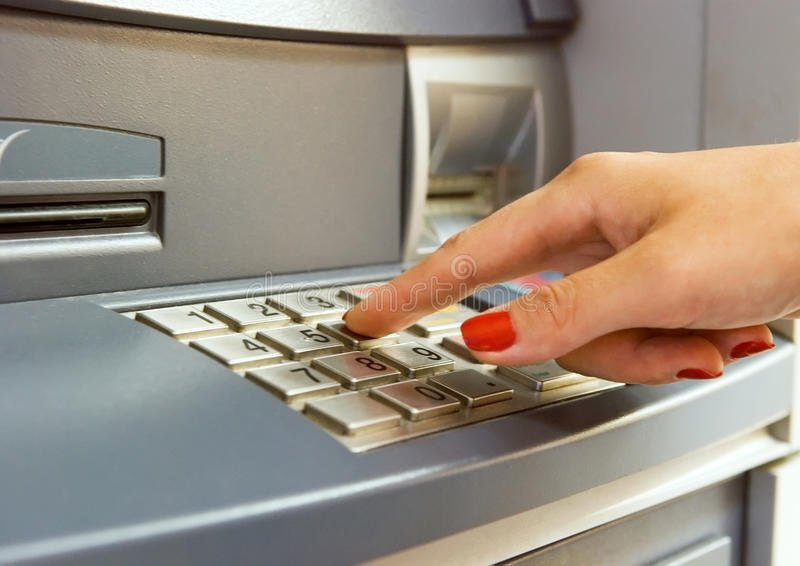 Using bank ATM. Woman's hand dialing pin on bank ATM keyboard