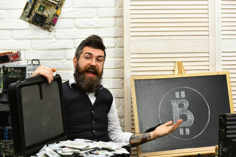 Using Bitcoin to transact is easy. Bearded hipster with bitcoin symbol and dollars. Bearded man with cash money stock image