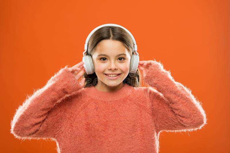 Using bluetooth wireless technology. Little child listening to music in bluetooth stereo earphones. Small girl wearing. Modern bluetooth headphones. Connecting stock images