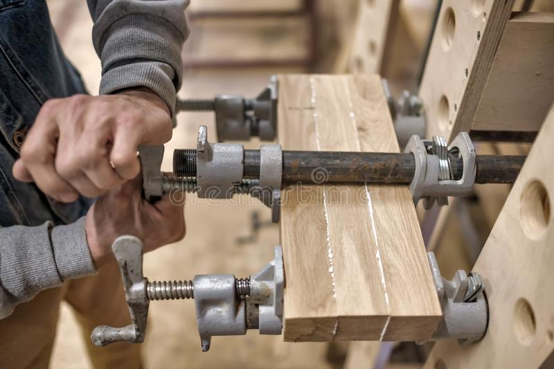 Using clamps and glue to connect wooden timbers for furniture detail. Joinery work. Using clamps and glue to connect wooden timbers for furniture detail royalty free stock photography