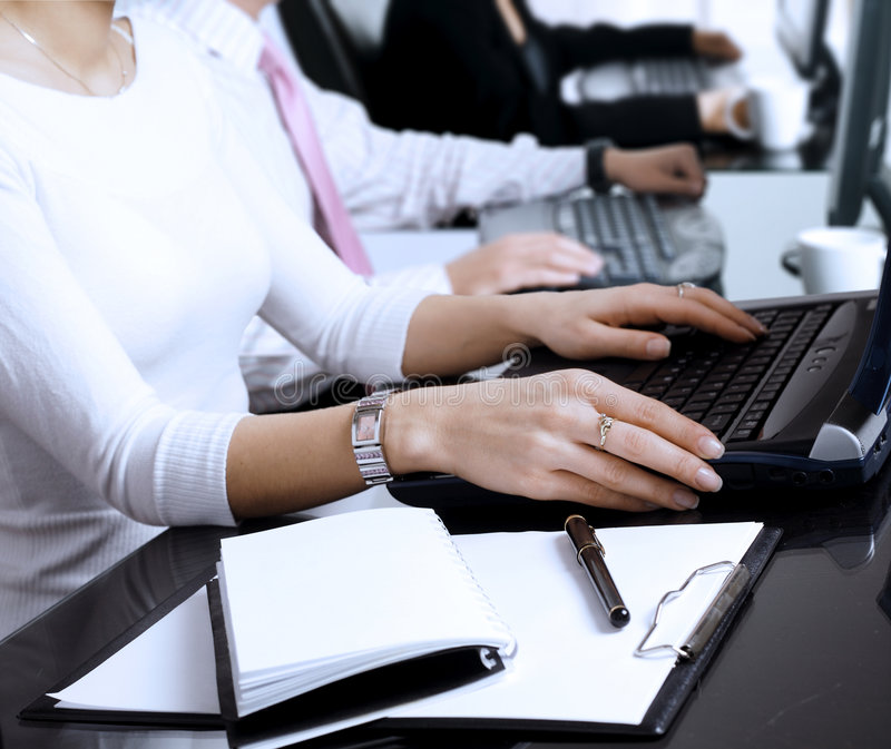 Using computer. Close-up os human hands. Young office workers are typing on keyboards in front of their office computers