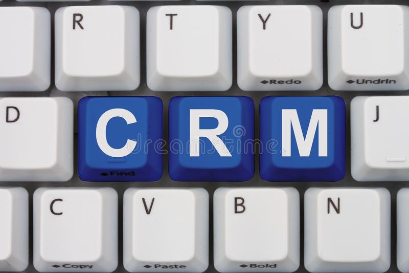 Using CRM software. A close-up of a keyboard with blue highlighted text CRM royalty free stock photo