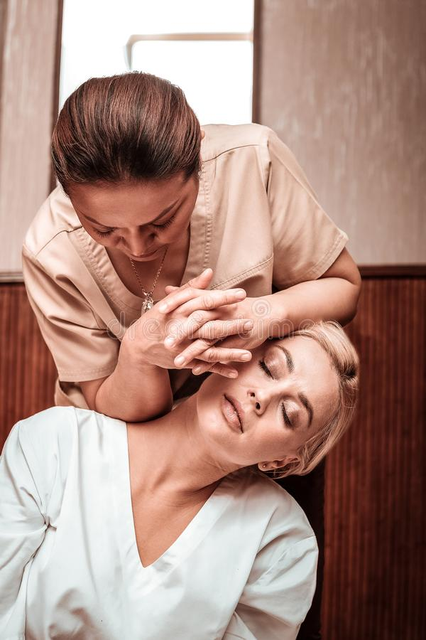 Concentrated woman massaging her client with her elbows. Using different techniques. Concentrared women with her fingers crossed massaging back and neck of her royalty free stock photos