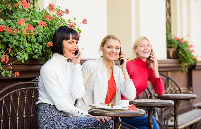 Using digital devices. Group women cafe terrace. Mobile addicted. Mobile conversation. Girls with mobile phones. Friends stock photo